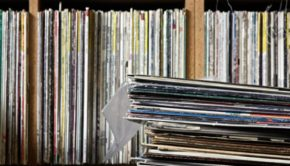 An old stack of records sits in front of a shelf full of vinyl in a local record store.